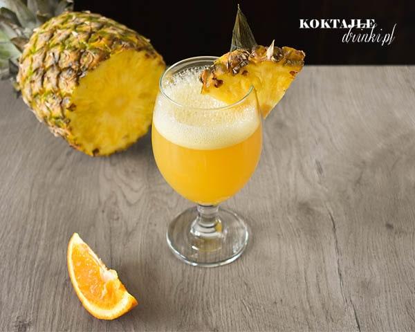 Widok z góry na drink z malibu, o żółtej barwie, spieniony z ozdobą w postaci ananasa.