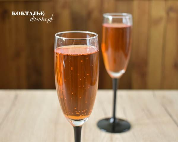 Drink Aperol Spritz widziany od frontu w dwóch kieliszkach o barwie jasno pomarańczowej.