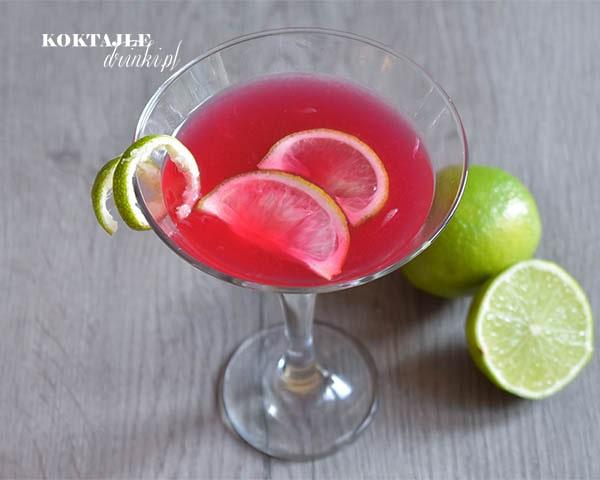 Bacardi Cocktail widziany z góry czyli drink o czerwonej barwie w kieliszku koktajlowym, ozdobiony twistem ze skórki limonki.