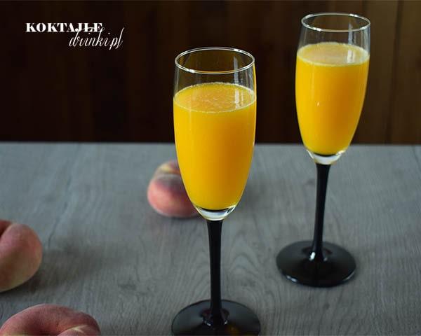 Drink Bellini o jasno żółtych barwach w dwóch kieliszkach od szampana.