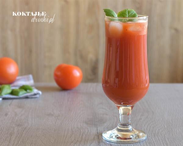 Drink z wódką Bloody Mary (Krwawa Mary) o barwie czerwonej w szklance ozdobionej listkami bazylii.