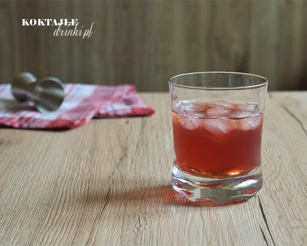 Drink Bloody Whisky w niskiej szklance o barwie jasno czerwonej z kostkami lodu.