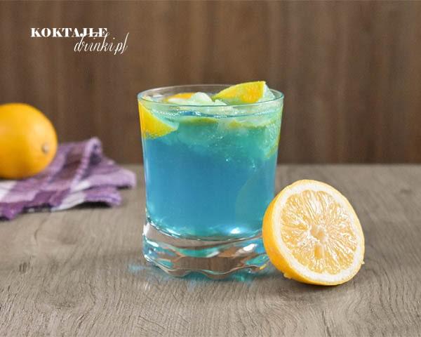 Blue Cider błękitny drink z wódką i cydrem przyozdobiony cytryną.