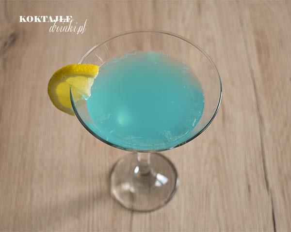 Widok z góry na drink z ginem, Blue Lady o błękitnej barwie w kieliszku ozdobionym kawałkiem cytryny.