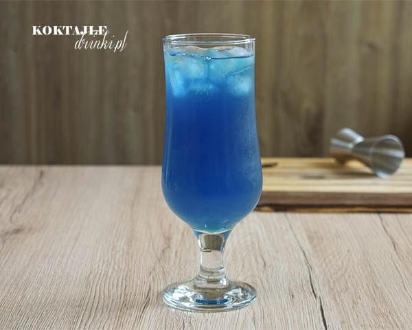 Widok na drink Blue Malibu od frontu o barwie niebieskiej z kostkami lodu w szklance.