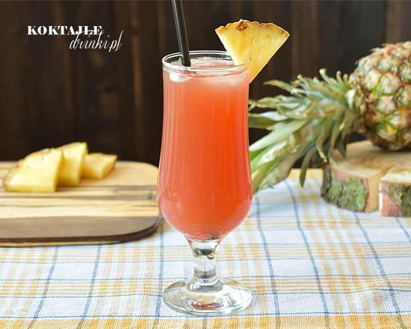 Drink z wódką Burnso Tropical jasno czerwony w szklance ozdobionej ananasem.