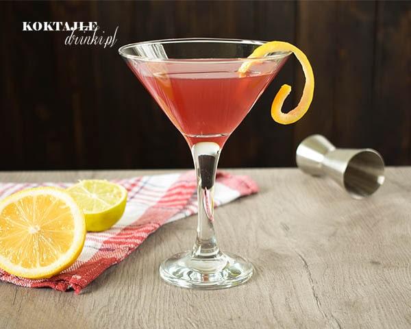 Drink z wódką, Cosmopolitan w kieliszku koktajlowym z twistem z cytryny, na drugim planie widoczne połówki cytryny i limonki.