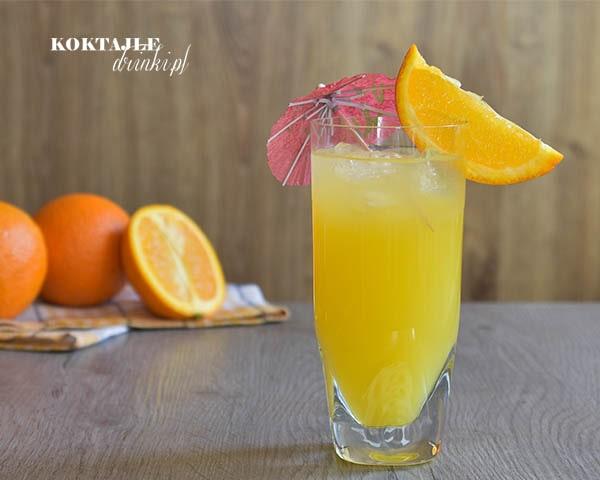 Drink z rumem, Cowboy Roy w szklance Collins o barwie jasno pomarańczowej, przyozdobiony plasterkiem pomarańczy i czerwoną parasolką.