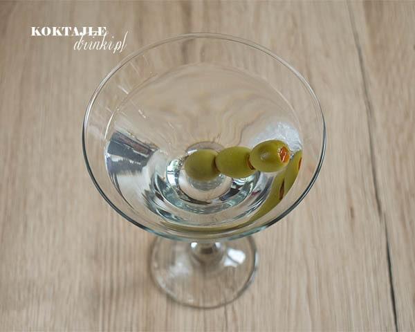 Drink Dry Martini w kieliszku o przezroczystej barwie z ozdobą 3 oliwek na wykałaczce.