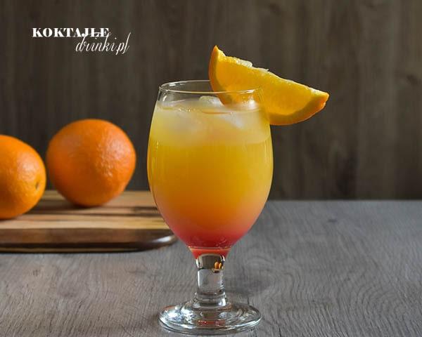 Widok od frontu na dwu warstwowy drink Gin Summer Night, czerwień na dole powoli ku górze łącząca się z pomarańczą.