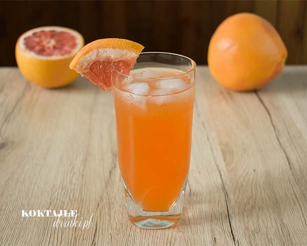 Drink z aperol, Grape Wild Aperol, o pomarańczowej barwie w wysokiej szklance ozdobionej kawałkiem grejpfruta.