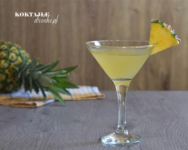 Havana Beach - drink z rumem w kieliszku koktajlowym w kolorze jasno żółtym ozdobiona kawałkiem ananasa.