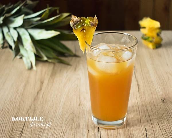 Drink Jager Na Tropikalnej Plazy o barwie ciemno pomarańczowej w szklance ozdobionej ananasem.