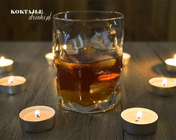 Drink Jagerbomb w otoczeniu świeczek w lekkim półmroku w niskiej szklance z kostkami lodu.