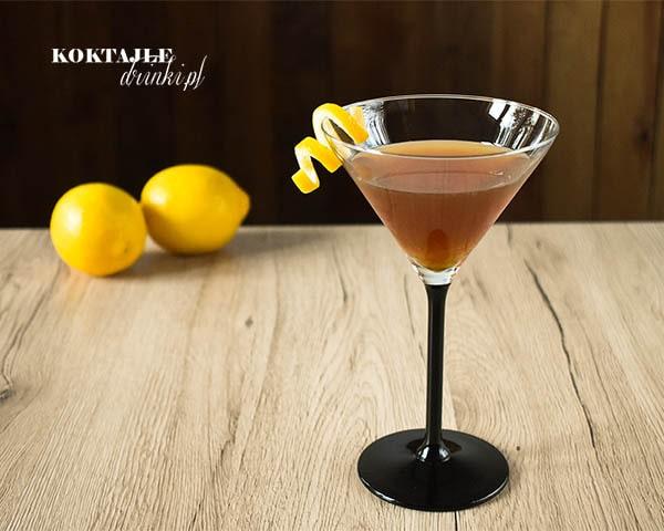 Drink Jagerita o jasno brązowej barwie w kieliszku koktajlowym z twistem ze skórki cytryny.