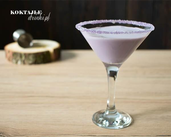 Drink Jagodzianka z malibu o jasno fioletowej barwie w kieliszku koktajlowych z fioletową crustą.