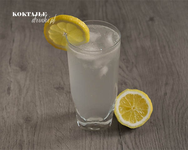 John Collins - drink z ginem w szklance ozdobionej kawałkiem cytryny, widok bardziej z góry.