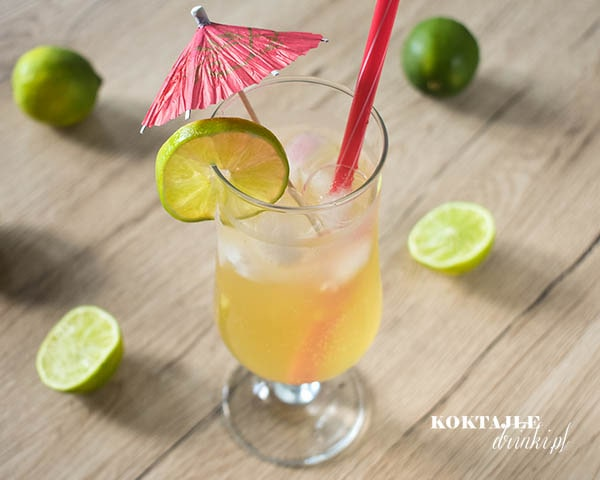 Drink Malibu Paloma o jasno żółtej barwie w ujęciu z góry w otoczeniu połówek limonek.