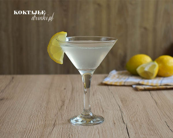 Drink Martini z wódką i spritem w kieliszku koktajlowym ozdobionym kawałkiem cytryny, w drugim planie cytryny.