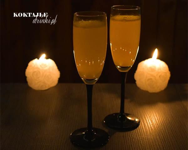 Dwa kieliszki drinka Mimosa, Mimoza z szampanem Prosecco, o pomarańczowej barwie w otoczeniu świec, przy zmroku.