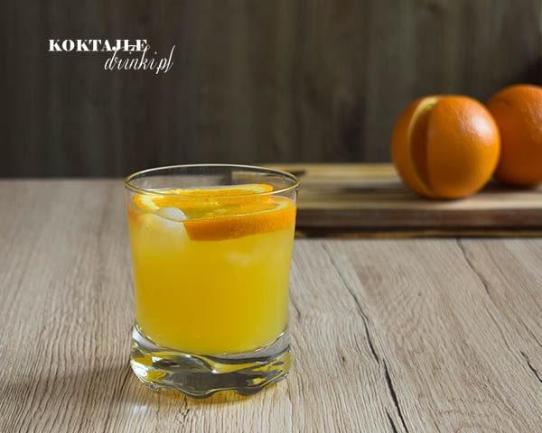 Mithering Bastard z whisky widziany od frontu o pomarańczowej barwie z kawałkami pomarańczy w szklance.