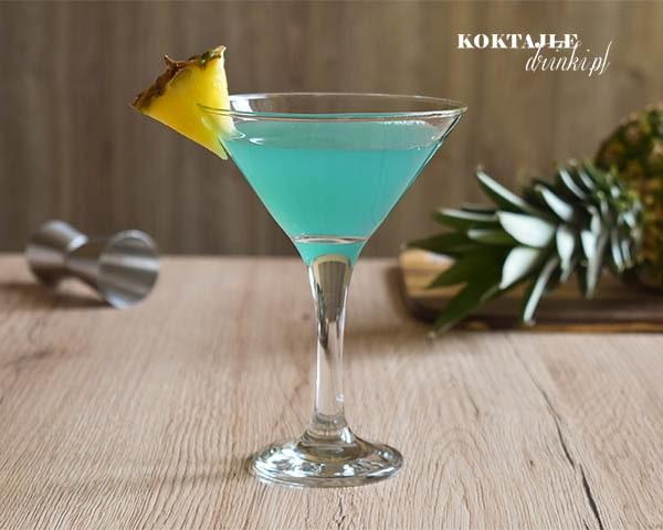Drink Rajski Ananas z malibu o barwie zielono niebieskiej w kieliszku przyozdobionym kawałkiem ananasa.
