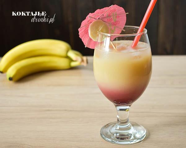 Drink Rajski Banan z malibu w dwu kolorowych warstwach, na dole czarną porzeczka, na górze banan.