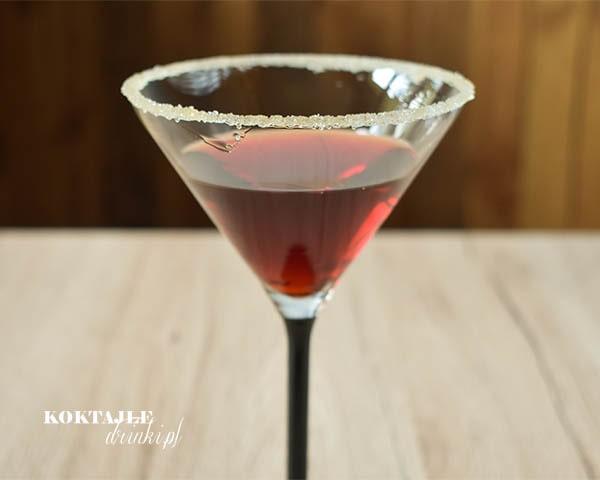 Ujęcie od frontu na drink Red Coffee z Jagermeister o barwie czerwonej, zbliżenie na crustę z likieru kawowego i cukru.