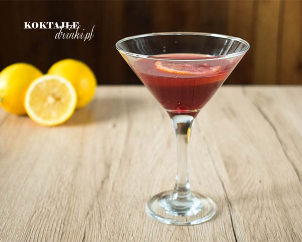 Drink Red Jager Sour w kieliszku koktajlowym o barwie czerwonej w otoczeniu cytryn.