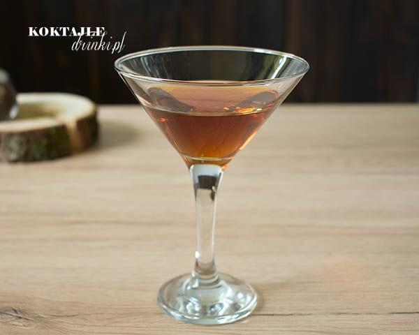 Drink z whisky Revolver o brązowej barwie w kieliszku martini, w tle widoczne kawałek drewna i kieliszek.