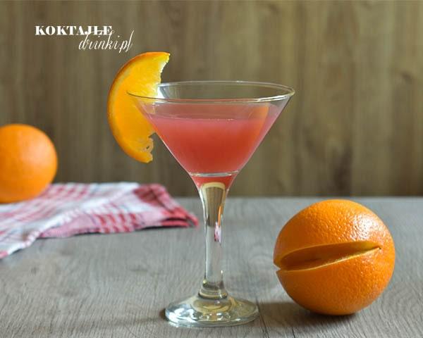 Drink Rum Cranberry o barwie czerwonej w szklance ozdobionej plastrem pomarańczy