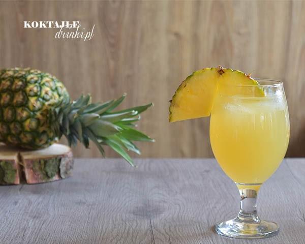 Drink z rumem, San Juan Cooler w pucharku ozdobionym kawałkiem ananasa, mający barwę żółtą ananasową.