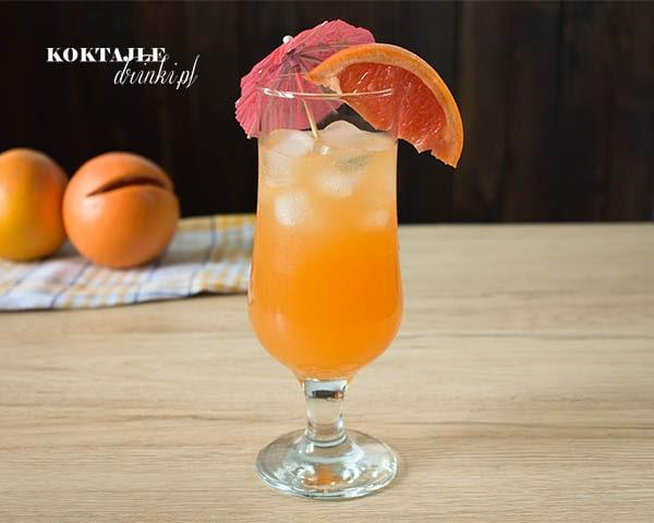 Drink Słoneczne Orzeźwienie w wysokiej szklance o pomarańczowej barwie ozdobiony kawałkiem grejpfruta i parasolką.