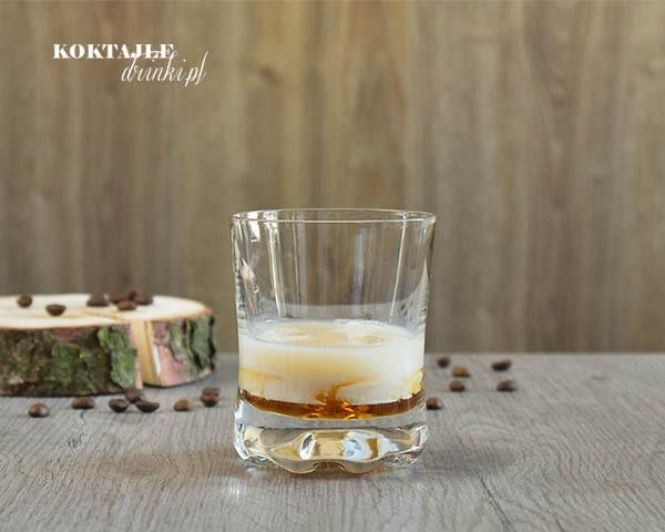 W drinku White Russian na samym spodzie widoczna wódka zmieszana z Kahlua tworząc złoty brąz na górze warstwa mleka