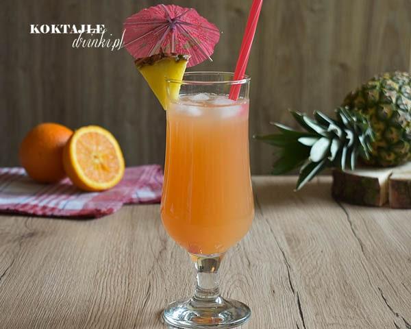 Zachód Słońca na Barbados, drink z malibu o barwie ciemno pomarańczowej w szklance ozdobionej ananasem i parasolką.