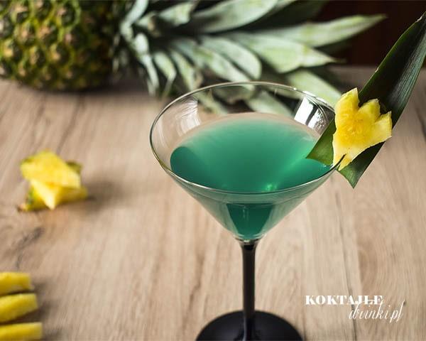 Drink z malibu o zielonej barwie w kieliszku ozdobionym kawałkiem ananasa.