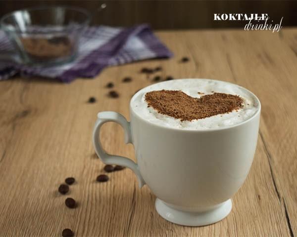 Kawa Caffe Latte z posypką czekolady na piance, na drugim planie widoczne naczynie z wiórkami czekolady.