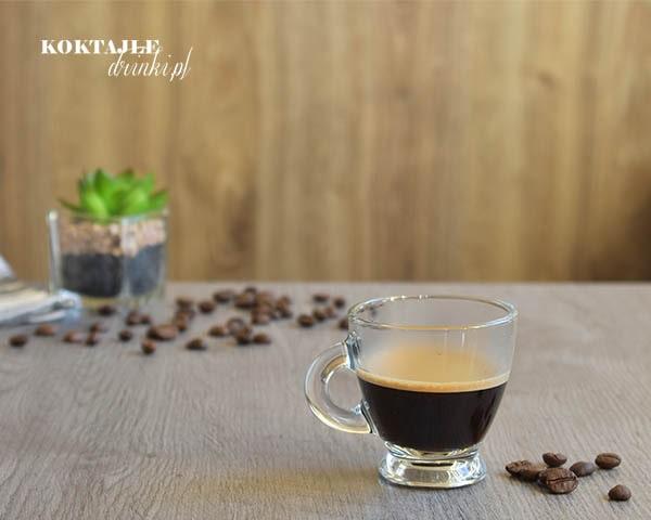 Kawa Espresso w małej filiżance z lekką pianką, na drugim planie ziarnka kawy.