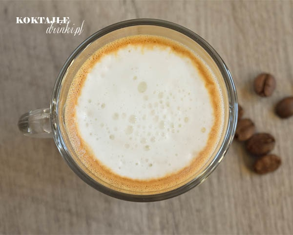 Widok z góry na Espresso Macchiato, zbliżenie na mleczną piankę, na drugim planie rozrzucone ziarna kawy.