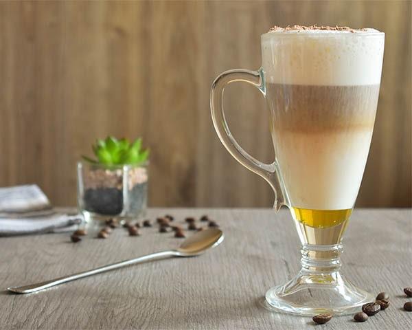 Latte Macchiato w cztero warstwowej odsłonie. Od dołu patrząc: miód, mleko, espresso, mleczna piana. Całość uwieńczona wiórkami czekolady.
