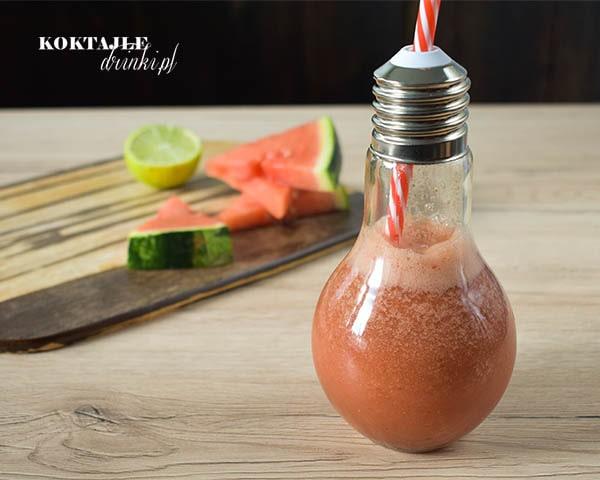 Koktajl owocowy smoothie o czerwonej barwie w szklance żarówce, w tle widoczne kawałki arbuza i połowa limonki.