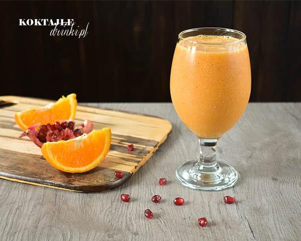 Koktajl owocowy smoothie o barwie pomarańczowej w otoczeniu ćwiartek pomarańczy i pestek granatu.