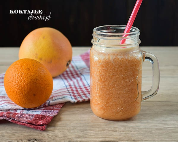 Koktajl owocowy smoothie o barwie pomarańczowej, na drugim planie pomarańcza z grejpfrutem.