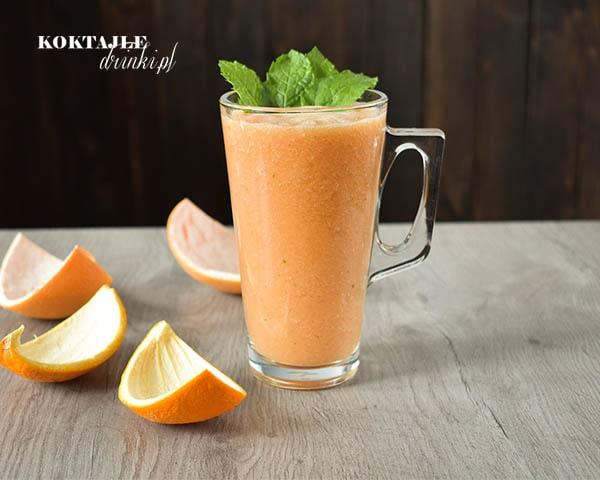 Koktajl owocowy smoothie o barwie pomarańczowej w szklance przyozdobionej miętą, obok leżą skórki pomarańczy oraz grejpfruta.