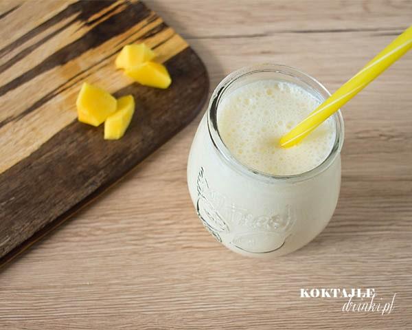 Koktajl owocowy smoothie o białej barwie w otoczeniu kawałków mango.