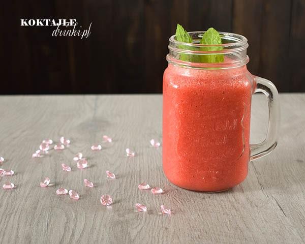 Koktajl owocowy smoothie o barwie czerwonej, w szklance z miętą na wierzchu, w otoczeniu różowych diamentów.
