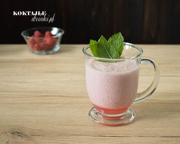 Koktajl smoothie owocowy o barwie jasno fioletowej w szklance ozdobionej liśćmi mięty.