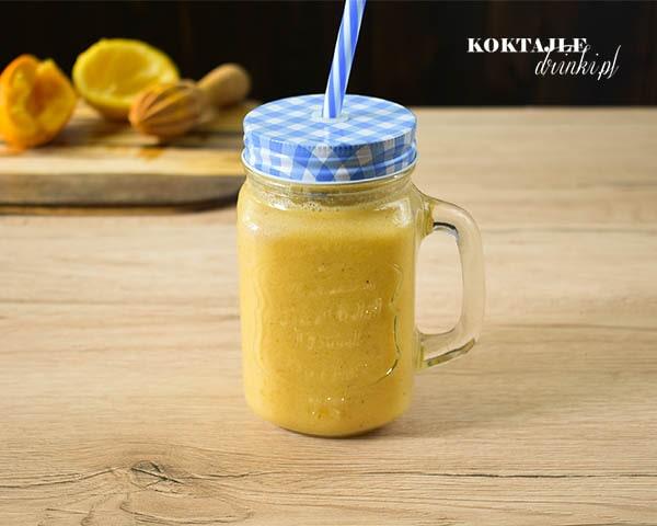 Koktajl owocowy smoothie o barwie ciemno żółtej, na drugim planie widoczne wyciśnięte pomarańcze.