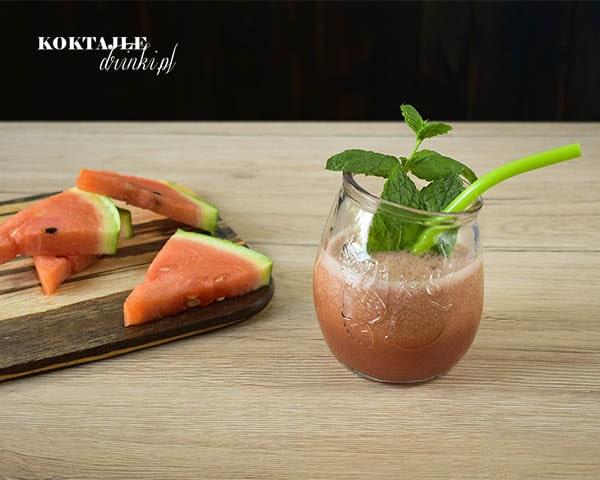 Koktajl owocowy smoothie o barwie jasno czerwonej w otoczeniu kawałków arbuza.