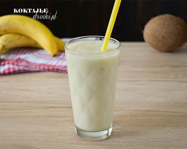 Koktajl owocowy smoothie o barwie białej, w tle kokos i banany.